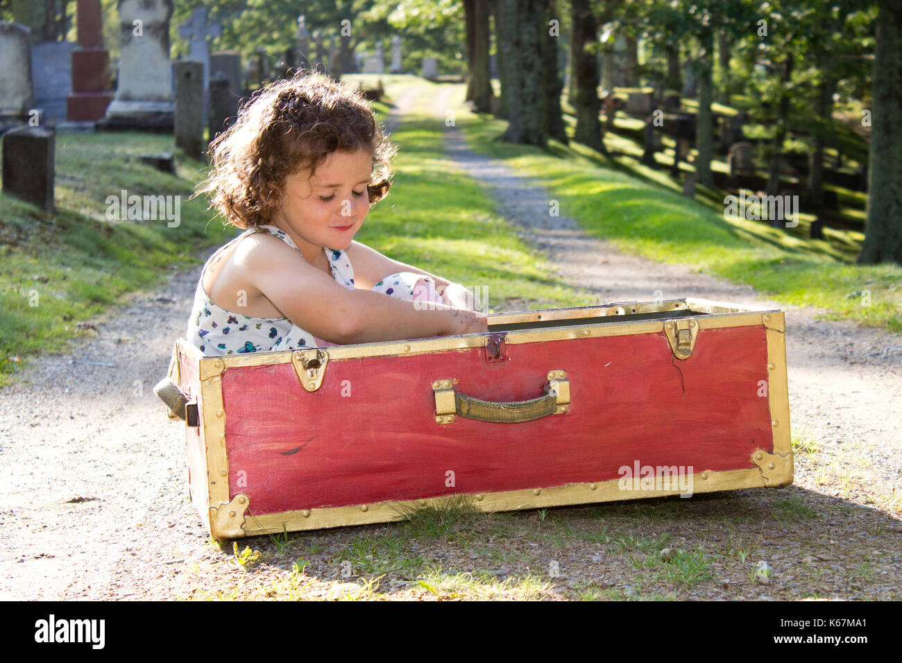 a small lonely girl in a red box in a cemetery - Stock Image
