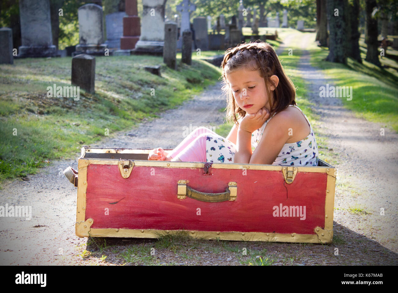 small child in a red box is sad in a graveyard - Stock Image
