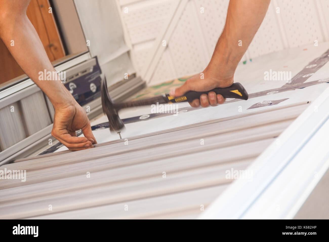 A construction worker hammering a nail to secure vinyl siding around a window in Ontario, Canada. - Stock Image
