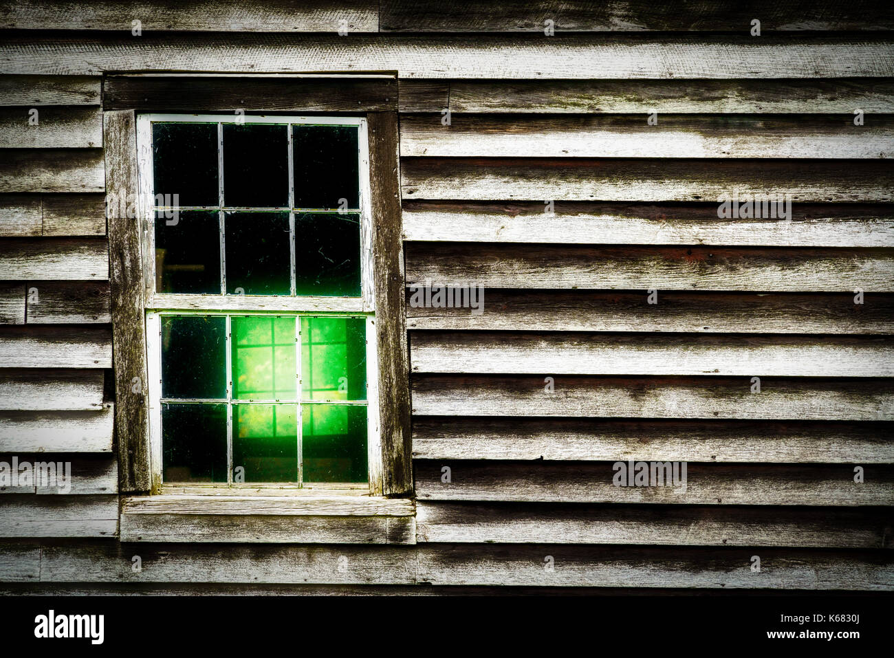 On a hill in Wisconsin, this old building is slanting and this window frame is taking most of it. - Stock Image