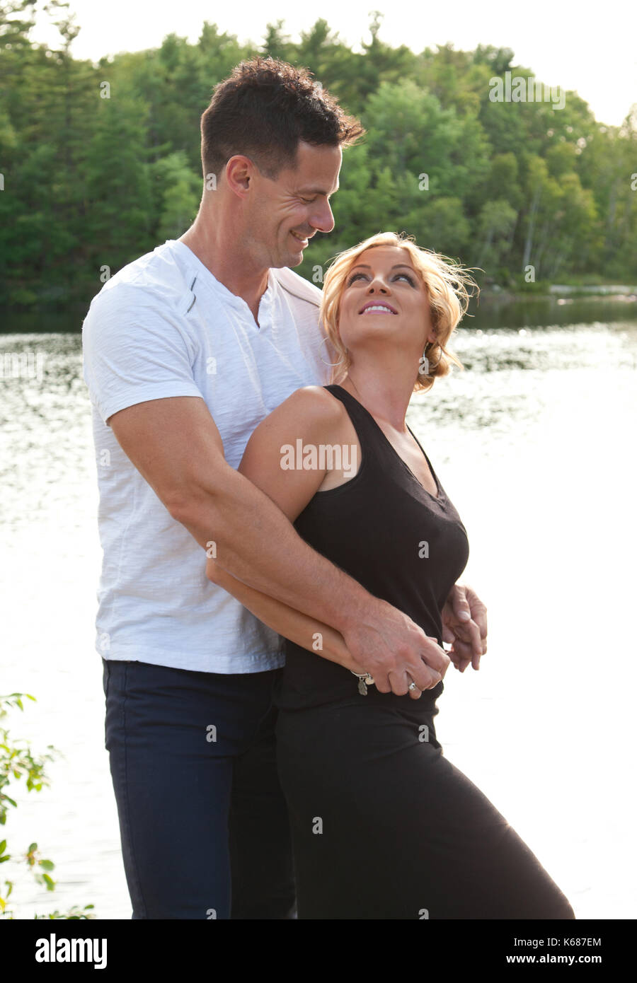 a dark haired man looks down and smiles at his beautiful blond wife by a lake - Stock Image