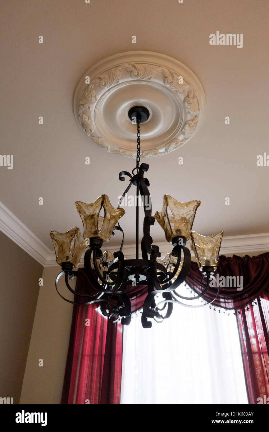 A Custom Made Golden Glass And Wrought Iron Chandelier Hanging By Majestic Red Curtains