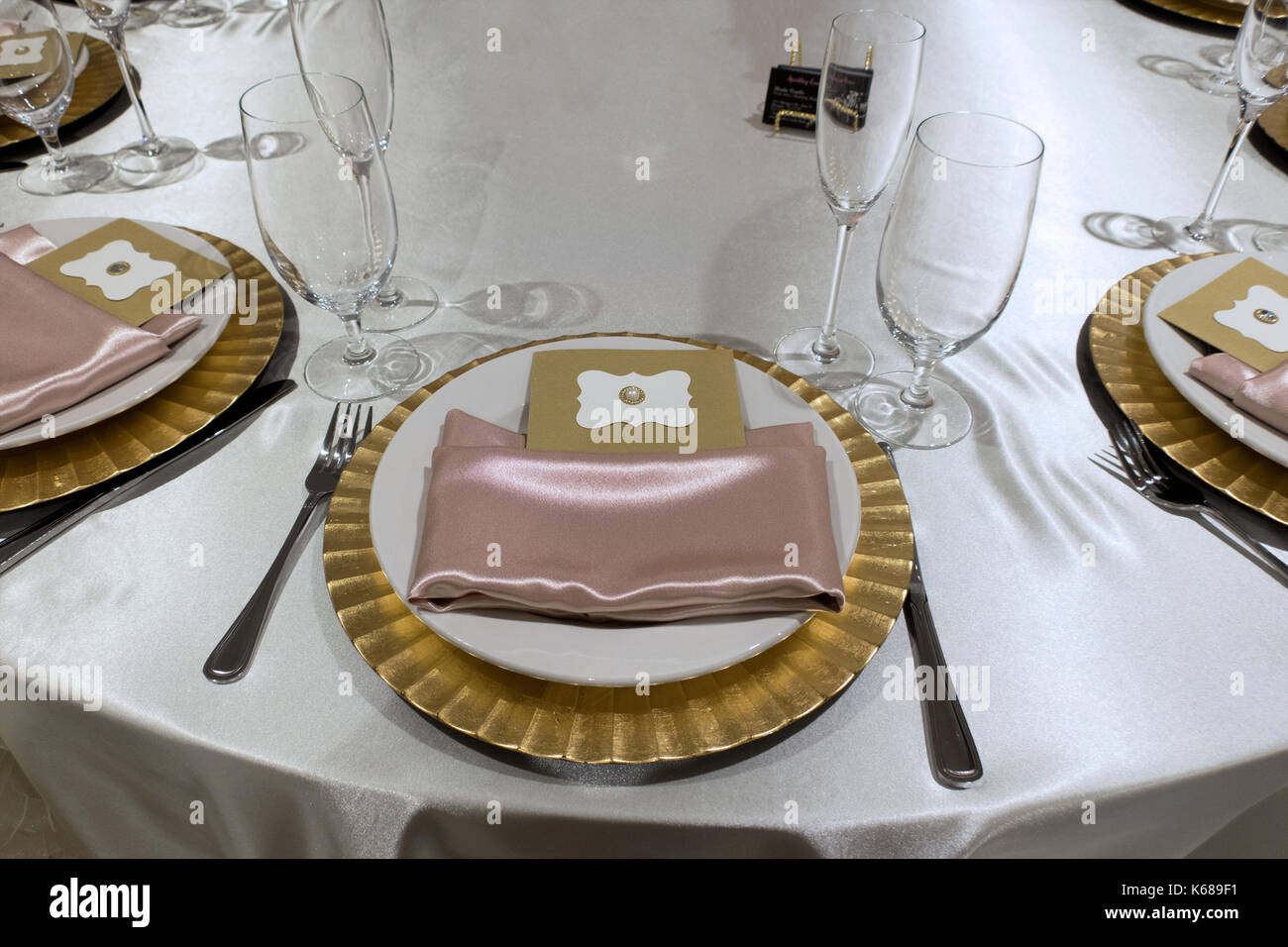 A fancy place setting with a golden plate pink napkins and an invitation card at a white satin tableclothed place. & A fancy place setting with a golden plate pink napkins and an ...