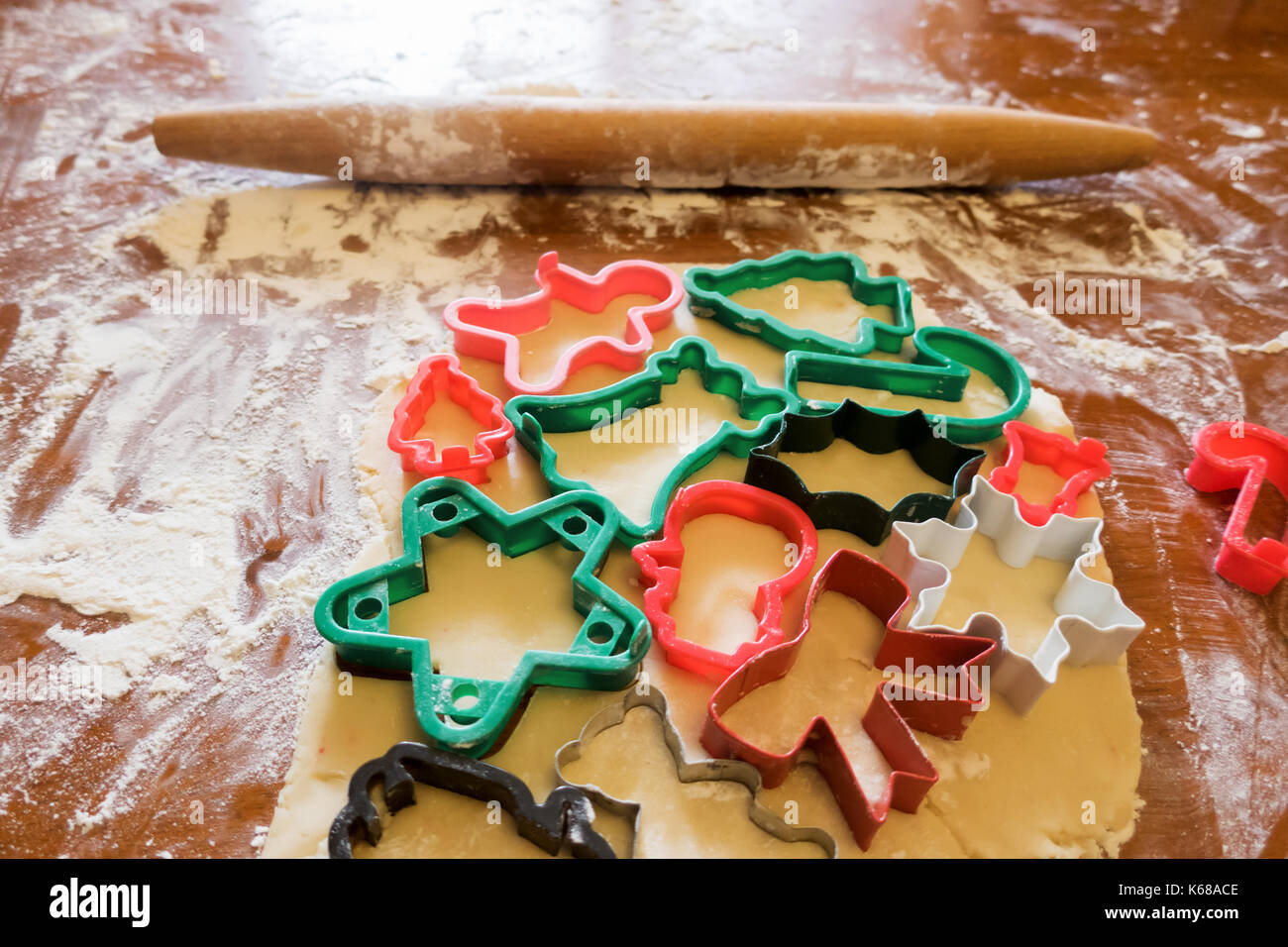 Christmas Cookie Cutters Stuck Into Sugar Cookie Dough On A Flowered