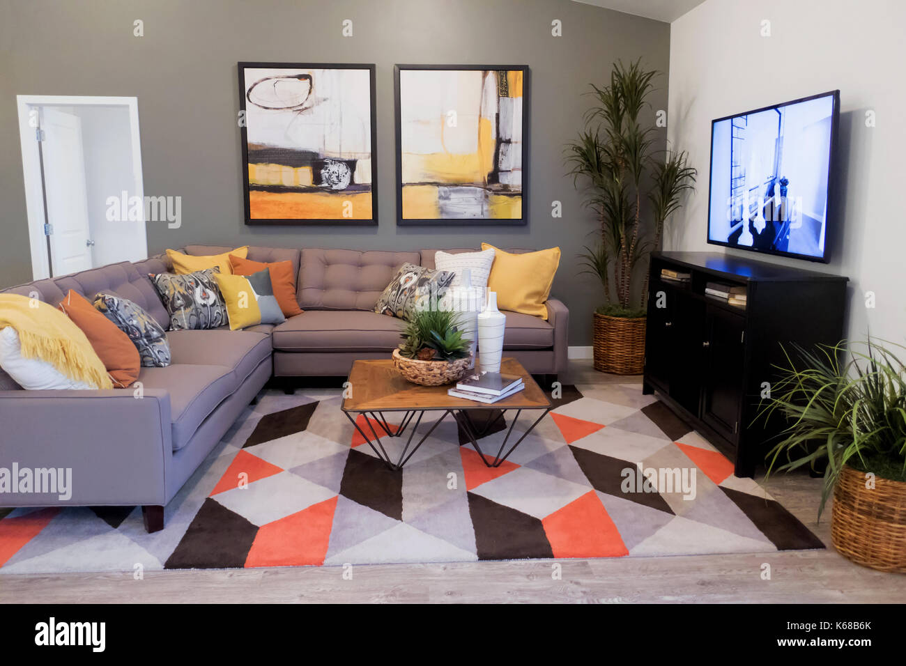 Wondrous A Gray Sectional Couch On A Colorful Rug Near A Tv Stand And Creativecarmelina Interior Chair Design Creativecarmelinacom