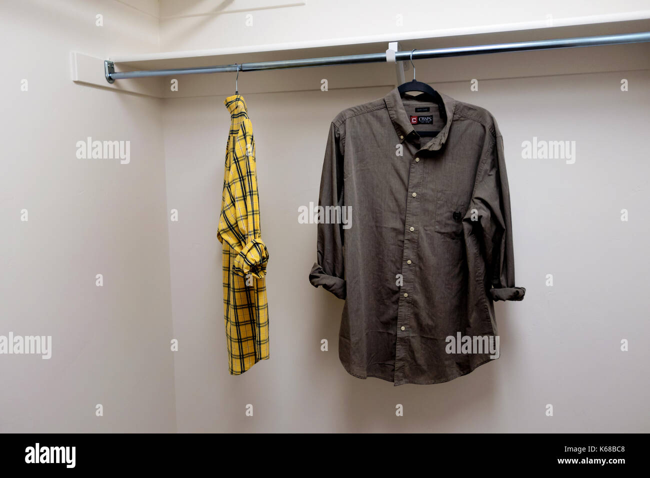 A walk-in closet full of men's short sleeved button up sleeves. - Stock Image