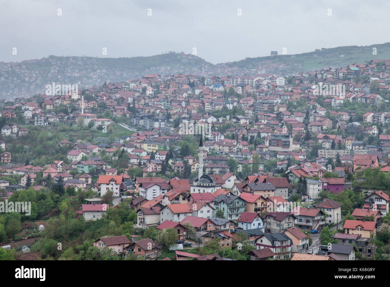 Aerial view of the hills of the suburbs of Sarajevo, Bosnia and Herzegovina during a cloudy and rainly day of spring. A mosque can be seen in front  P - Stock Image