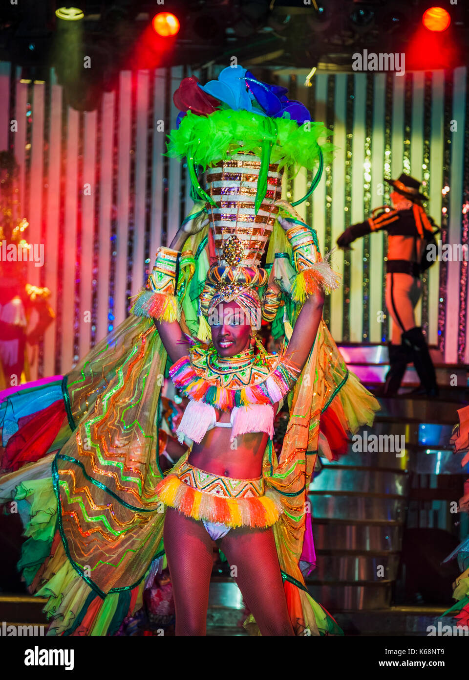 Local exotic dancers performing live on stage in flamboyant colourful costumes in a cabaret show for tourists in a nightclub in Havana, Cuba - Stock Image