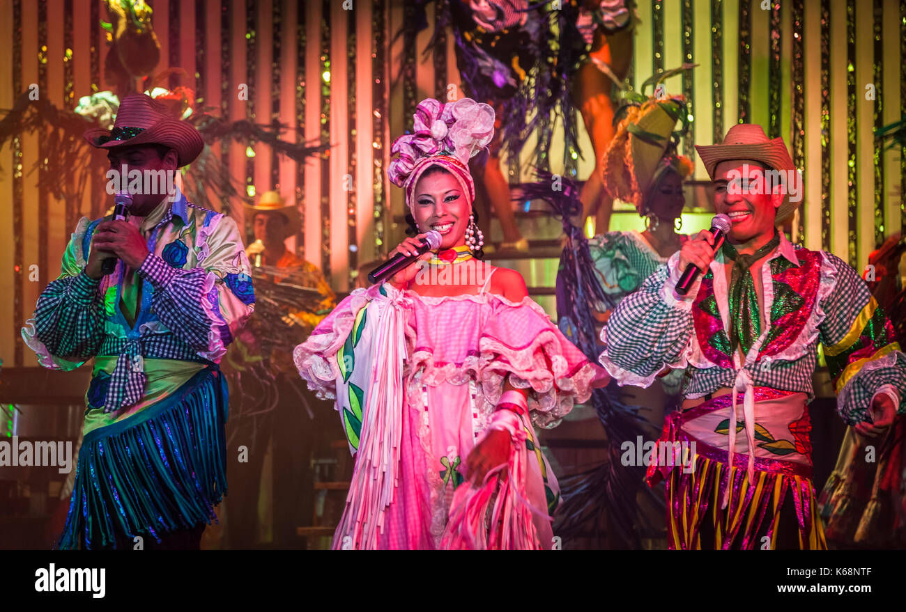 Local exotic dancers performing live on stage in colourful costumes in a cabaret show for tourists in a nightclub in Havana, Cuba - Stock Image
