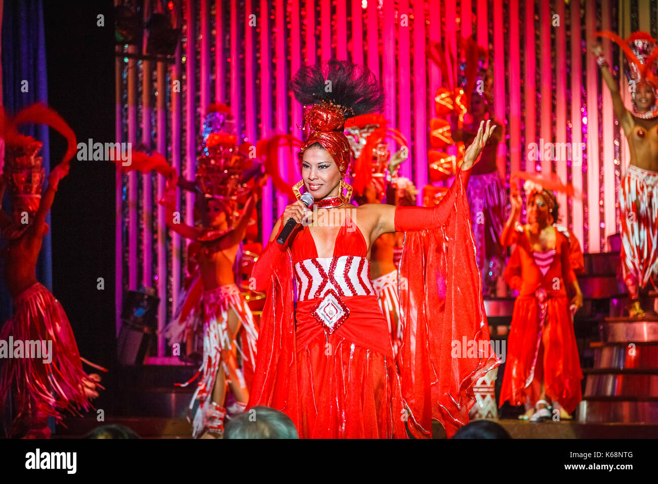 Singer in red dress and exotic dancers performing live on stage in colourful costumes in a cabaret show for tourists in a nightclub in Havana, Cuba - Stock Image