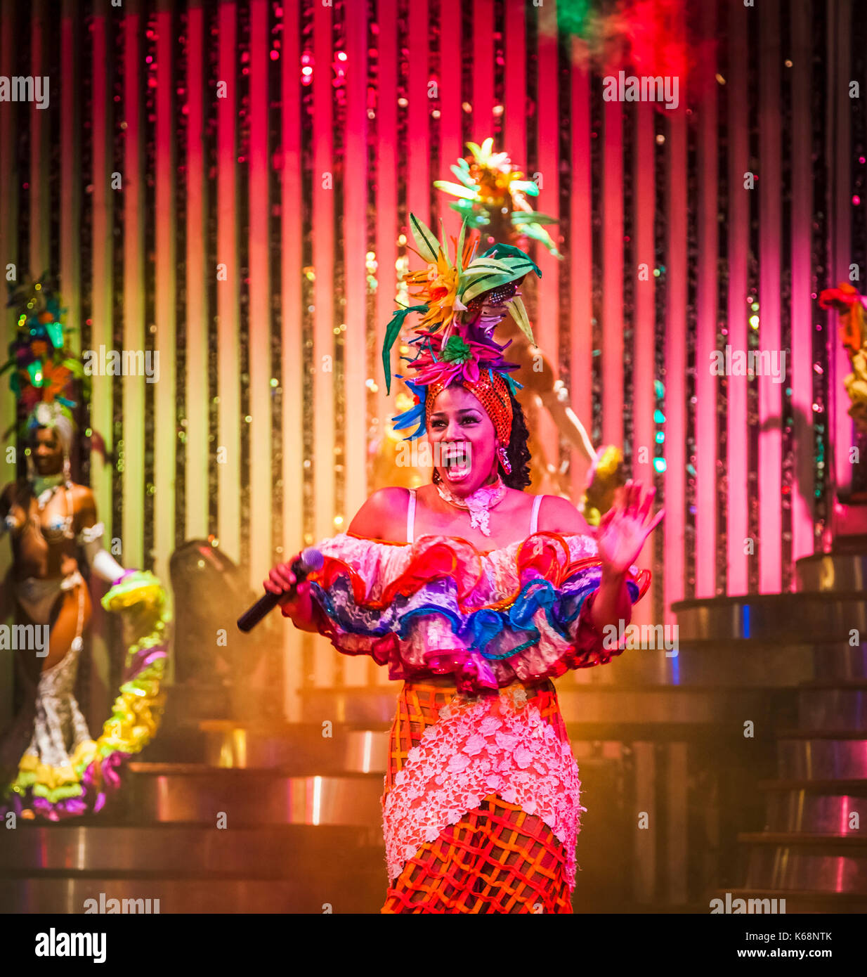 Exuberant singer and exotic dancer performing live on stage in colourful costumes in a cabaret show for tourists in a nightclub in Havana, Cuba - Stock Image