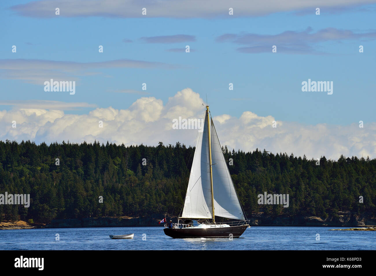 A sail boat glides through the calm waters of the Strait of Georgia near Vancouver Island British Columbia Canada. - Stock Image