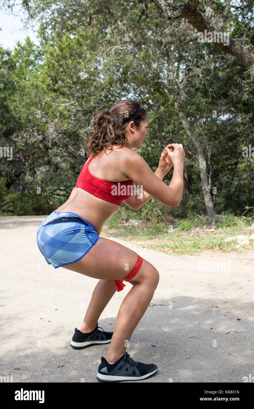 Young woman working out on her drive wearing red sports bra and shorts doing squats - Stock Image