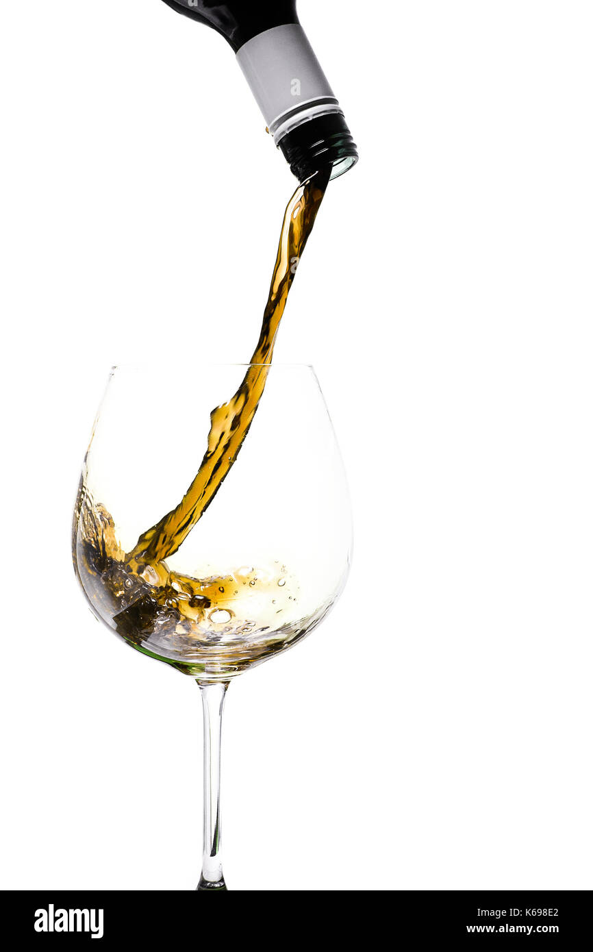 wine pouring into glass, yellow colour - Stock Image