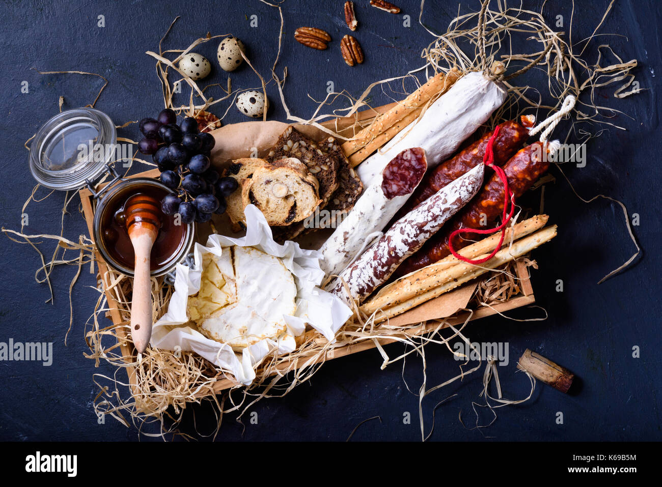 Antipasto appetizer prepared in a wooden box. Top view, blue background. - Stock Image