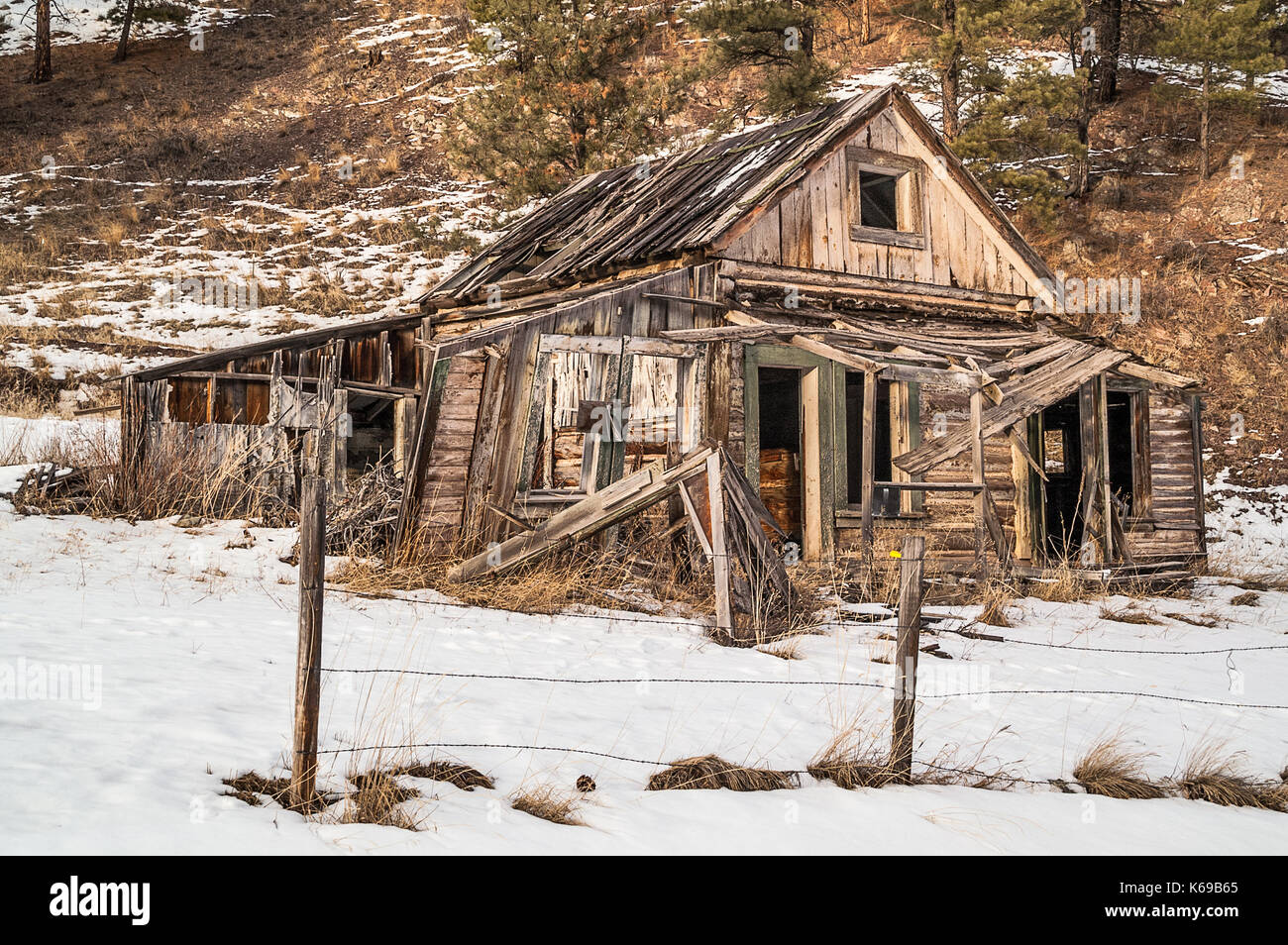Dilapidated home showing years of neglect in the evening sun - Stock Image