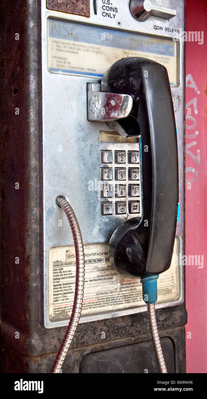 Abandoned coin operated public telephone with coin release slot. - Stock Image
