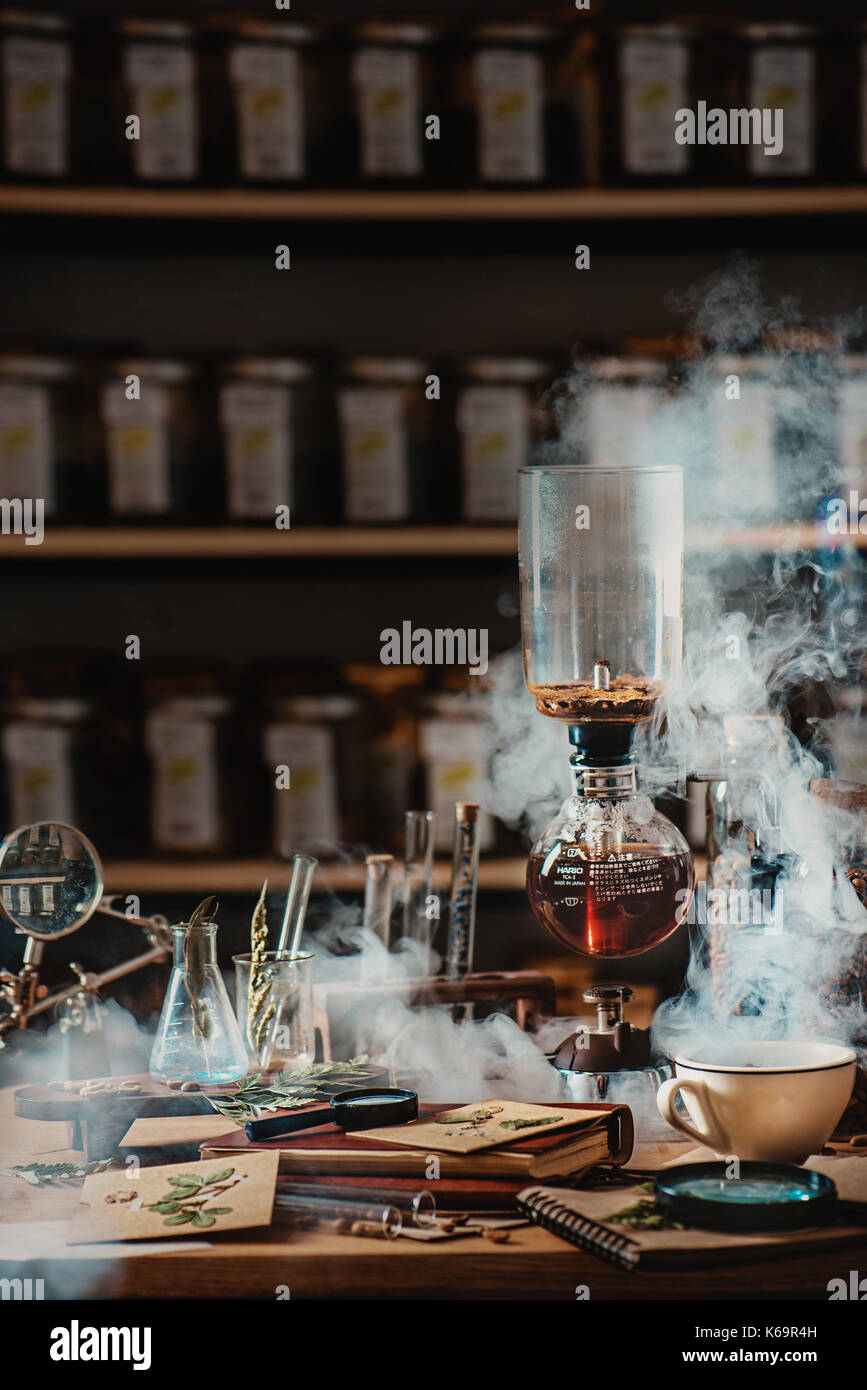 Brewing coffee in vacuum coffee maker with rising steam and a floral still life. Alternative coffee brewing method. Stock Photo