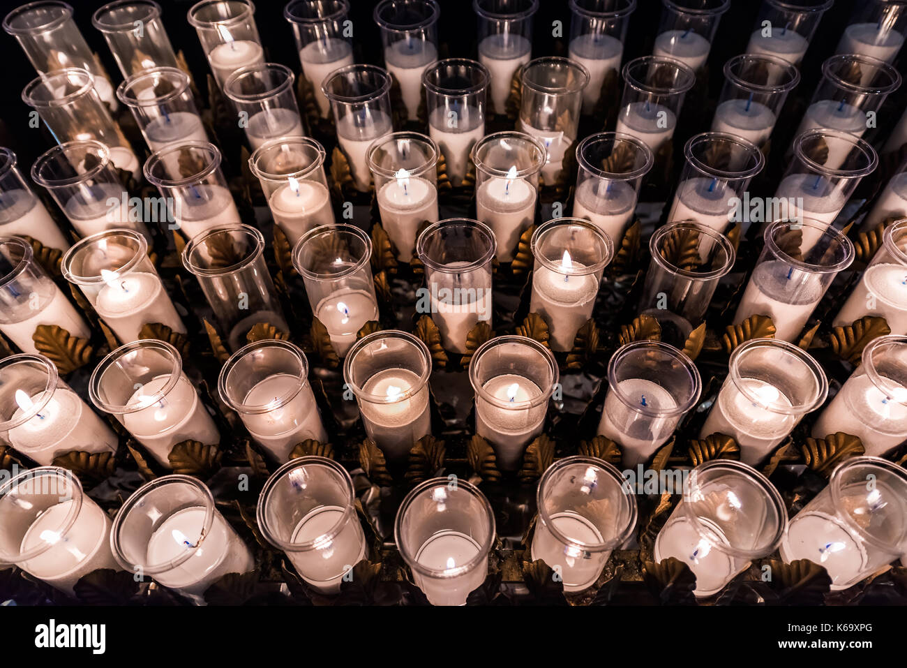 Closeup pattern of many white religious votive candles with yellow flame in church or cathedral - Stock Image