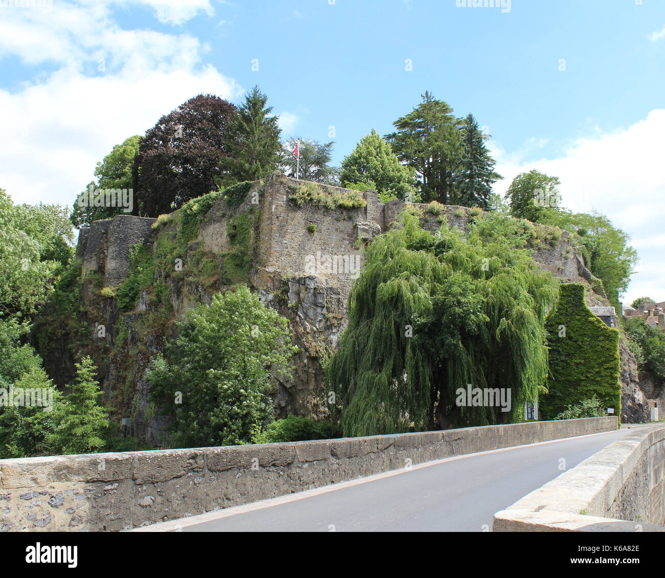 View of the ruins of the medieval Chateau Fresnay, from the bridge over the River Sarthe in Fresnay-sur-Sarthe in France. - Stock Image