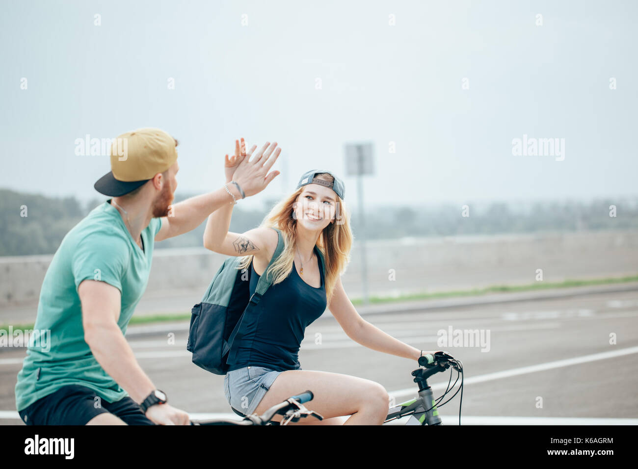 Fit cyclist couple standing at the summit high fiving on a sunny day Stock Photo