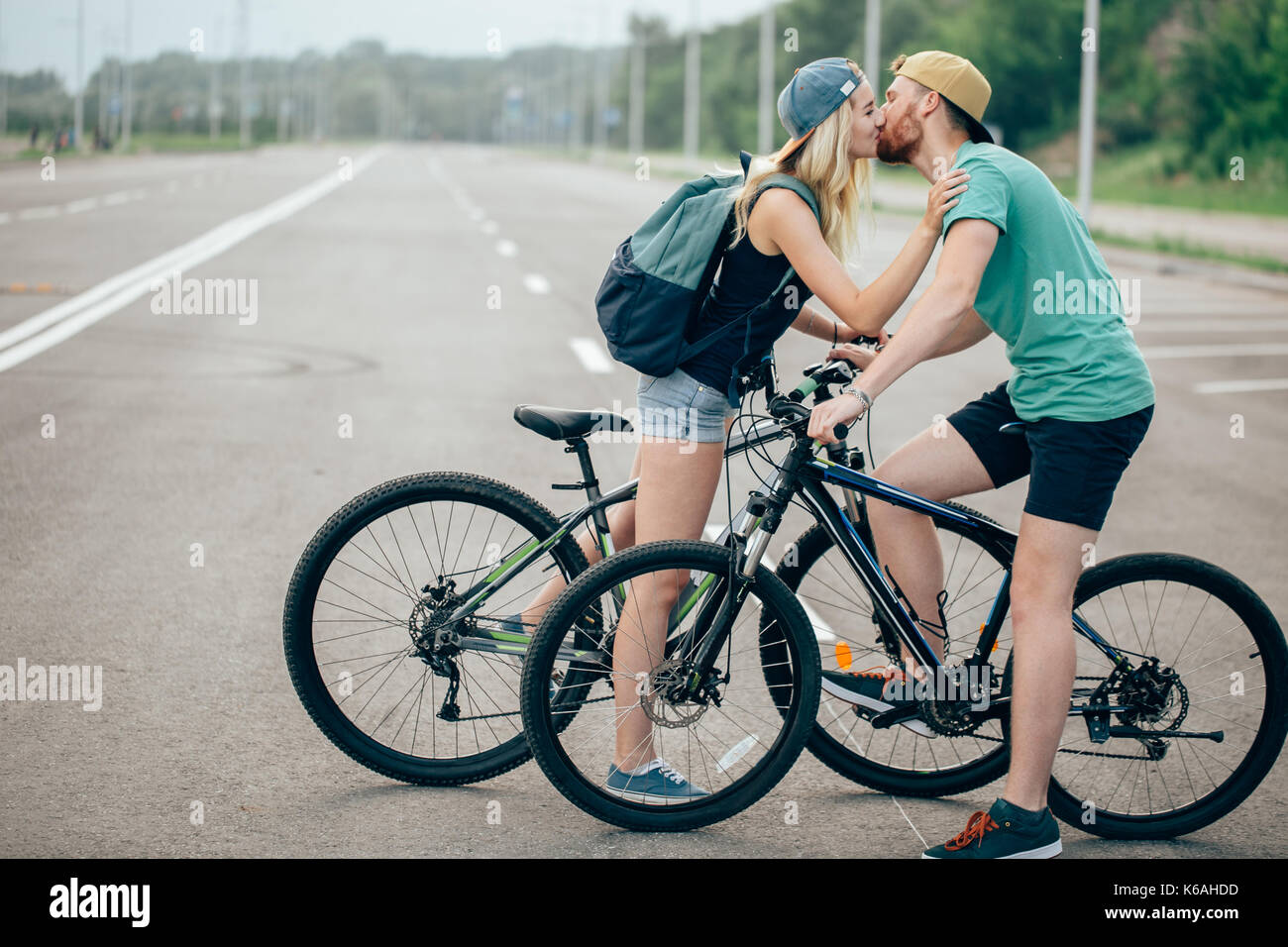 Beautiful young couple in love walking with bicycles, kissing and hugging. Stand near the bikes. The concept of active rest - Stock Image