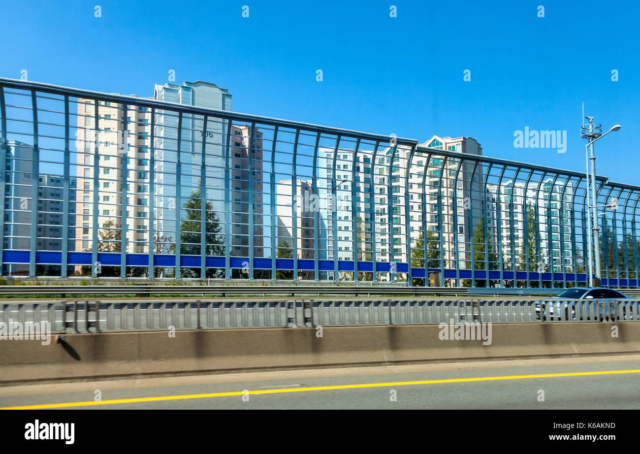 High barriers separate traffic lanes and shelter high rise apartments on Jeju Island in South Korea - Stock Image