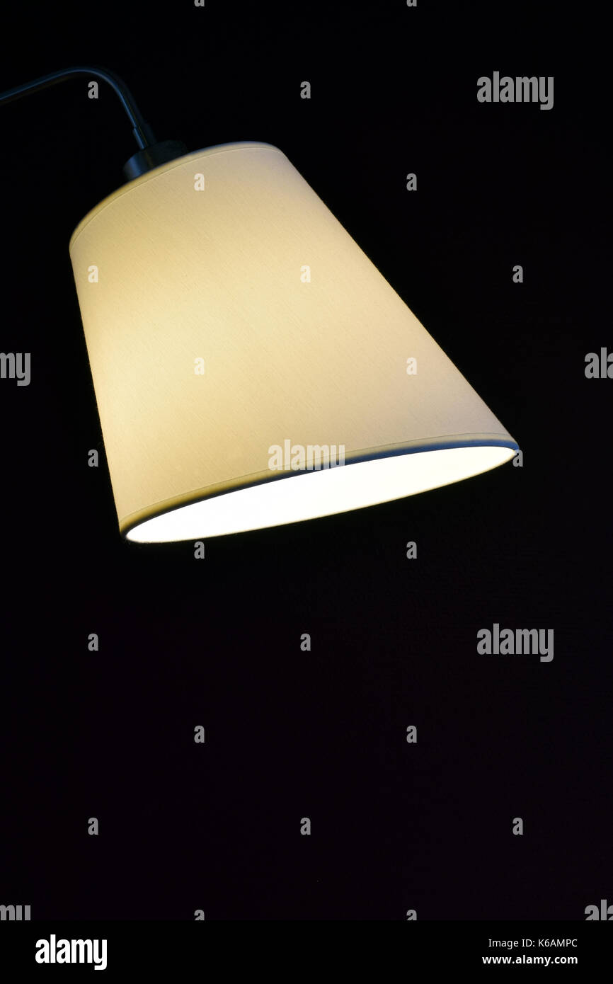 Simple but beautiful lampshade with light on black background vertical image with room for text