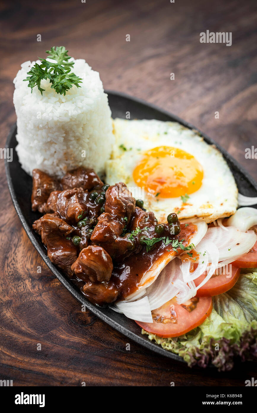 cambodian traditional khmer beef lok lak meal on wooden table - Stock Image