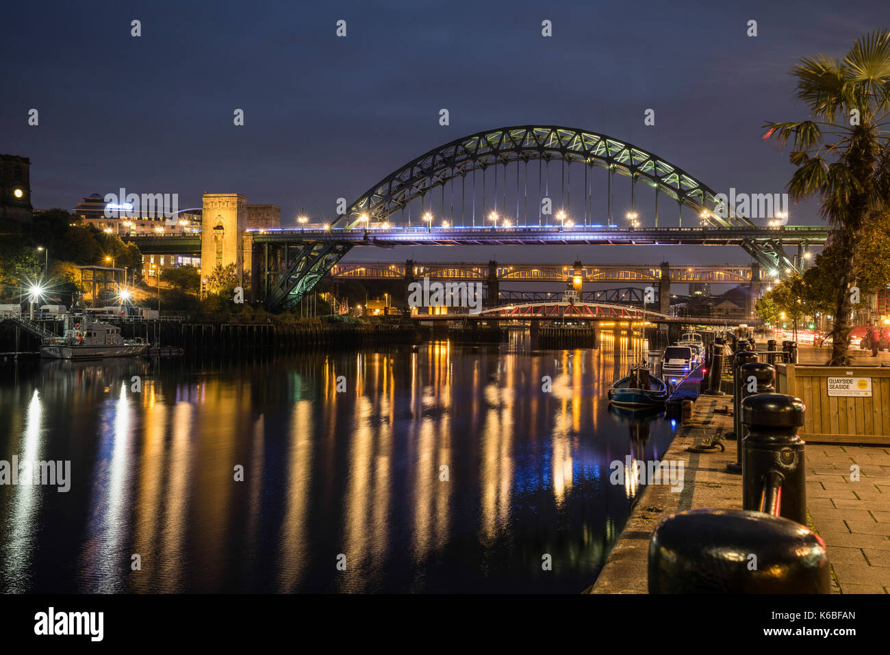 The Newcaste-Upon-Tyne/Gateshead quayside at night, showing the Tyne bridge and reflections in the River Tyne Stock Photo
