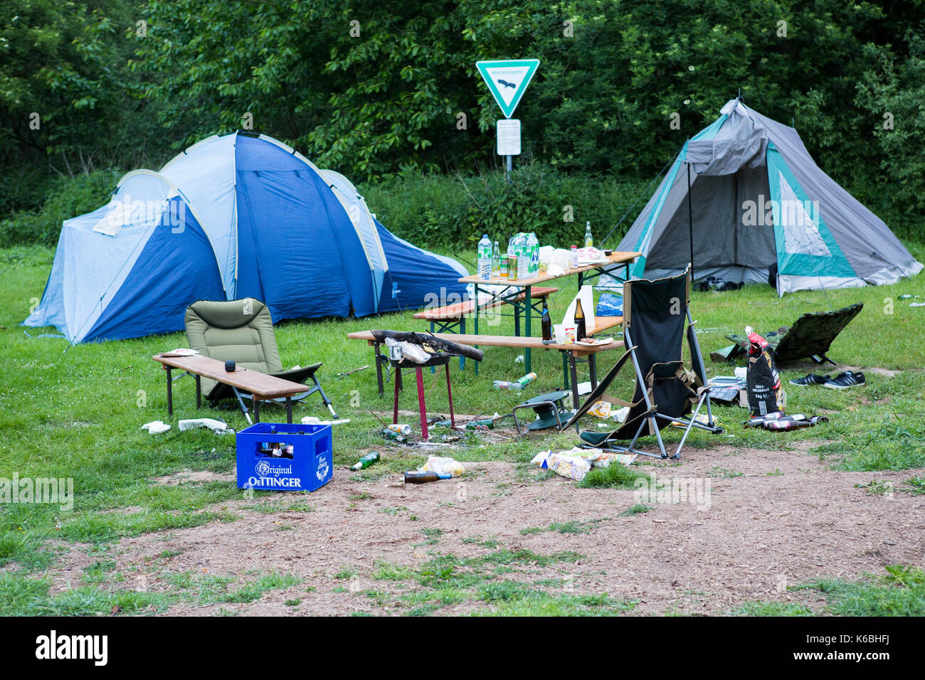 Campsite with tents left in complete mess / debris strewn after party - Stock Image