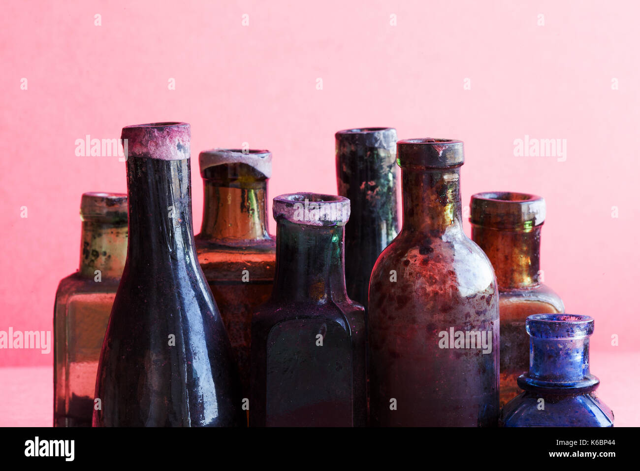 Retro design bottles macro view. Colorful dirty glass flacon set. Pink background, shallow depth of field, copy space. - Stock Image