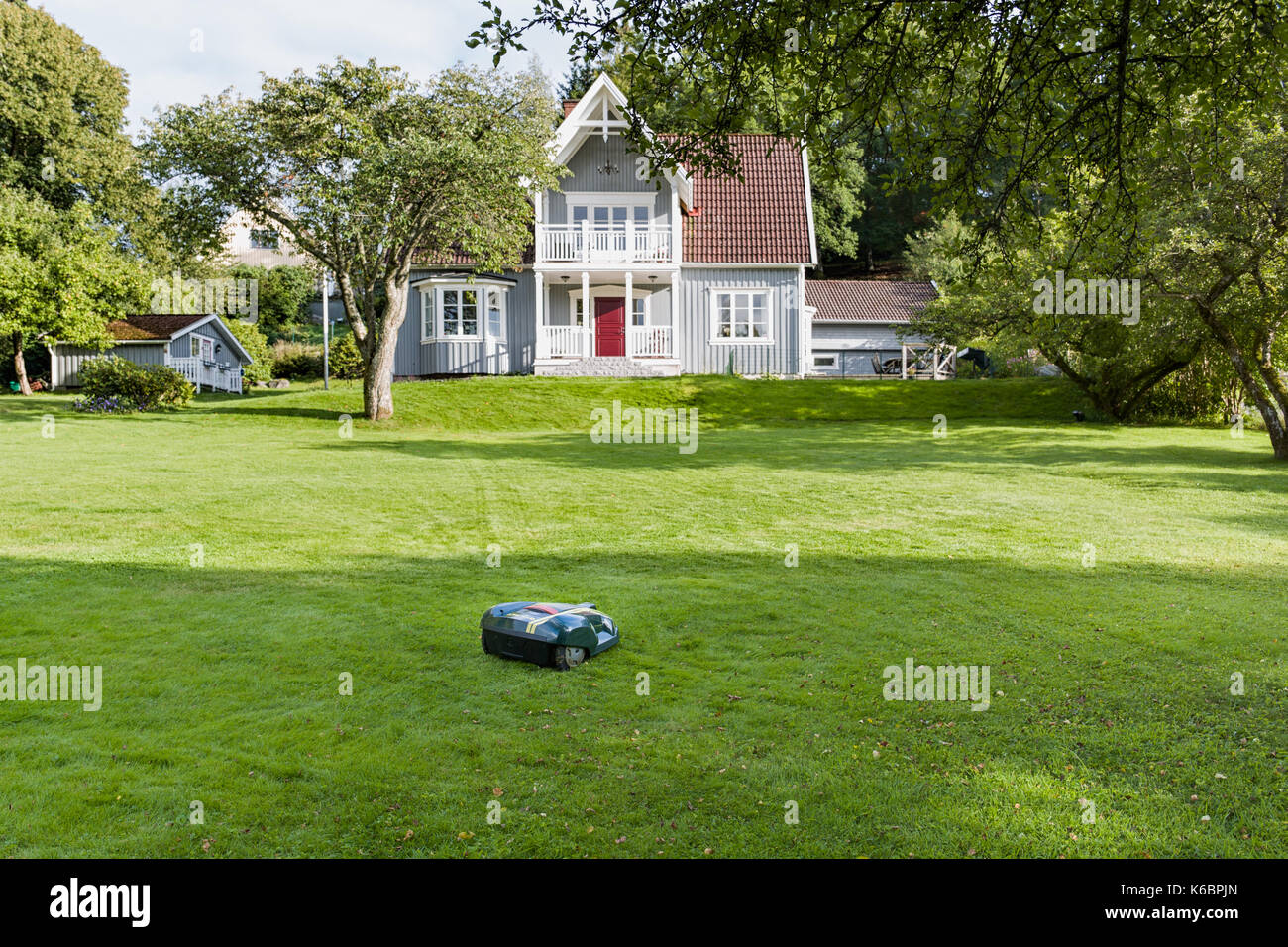 Robotic lawnmower on grass lawn in beautiful garden in front of idyllic wooden house  Model Release: No.  Property Stock Photo