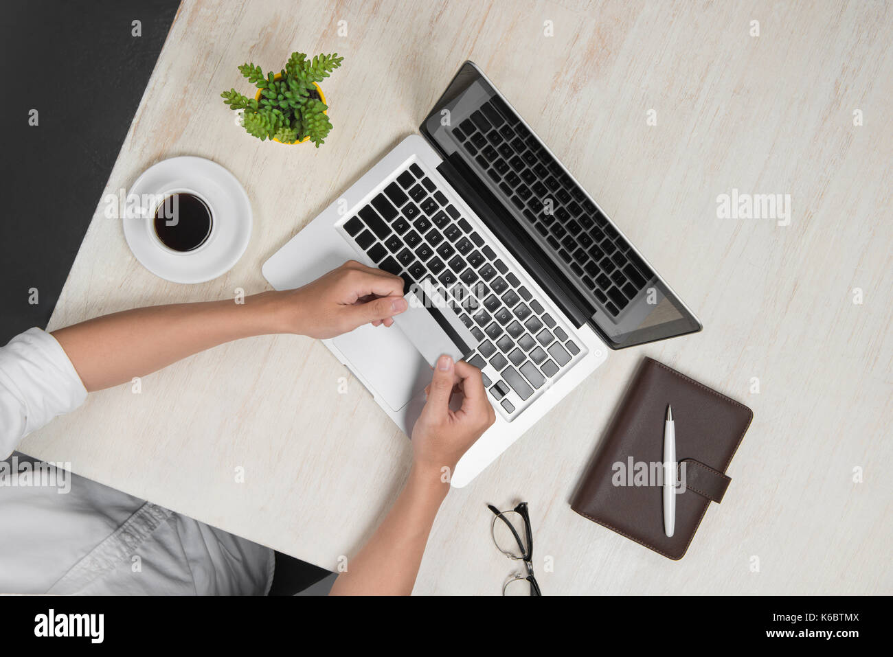Top view of man using a modern portable computer in home office shopping with credit card - Stock Image
