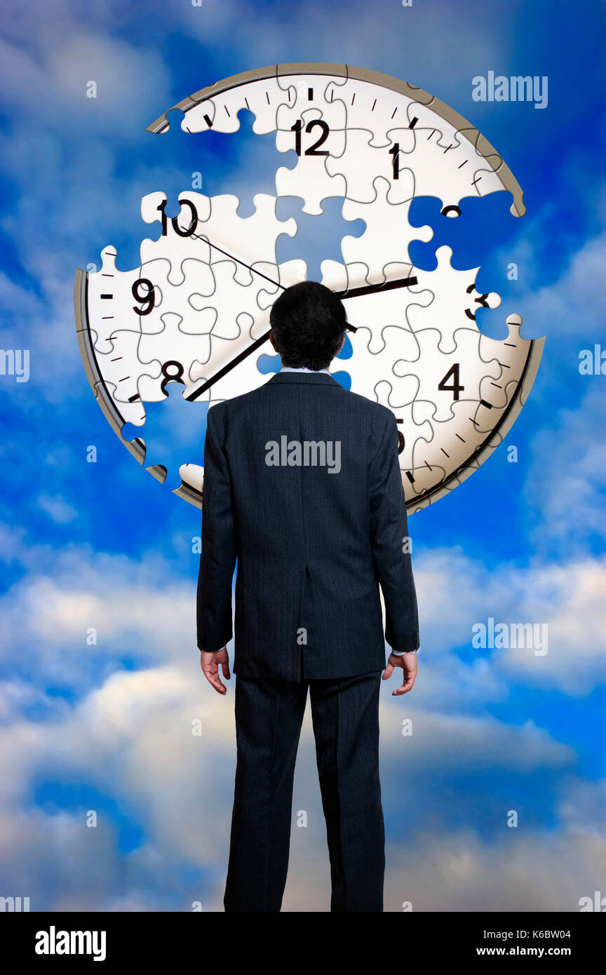 businessman in front a of a clock puzzle unfinished, time fly away concept - Stock Image