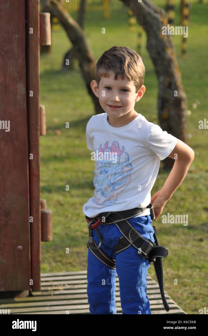 boy climbing on the wall mountaineer in the harness K6C5KB boy climbing wall harness stock photos & boy climbing wall harness