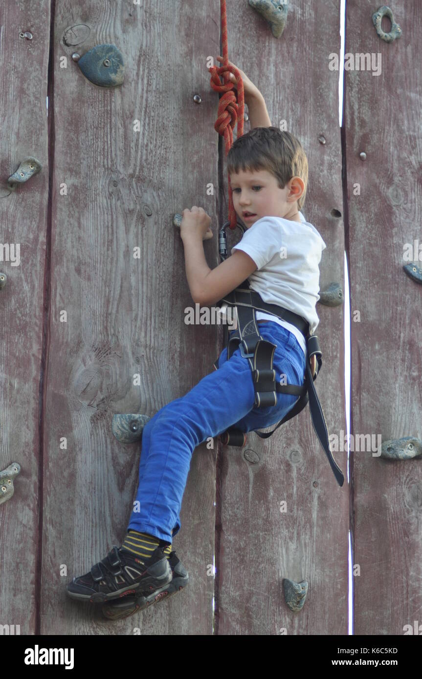boy climbing on the wall mountaineer in the harness K6C5KD boy climbing wall harness stock photos & boy climbing wall harness