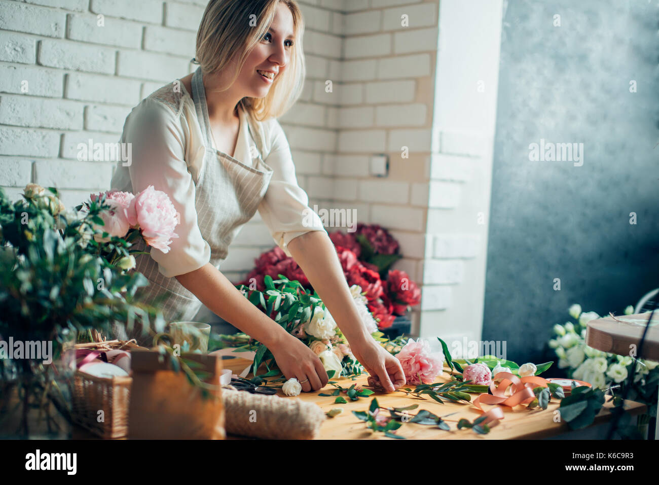 Florist workplace: woman arranging a bouquet with roses, matthiolas, ranunculus flowers and gypsophila paniculata twigs. - Stock Image
