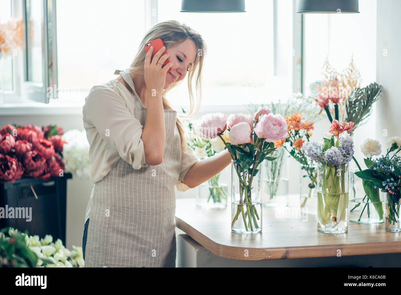 Portrait of young female florist talking on phone and making notes at flower shop. - Stock Image