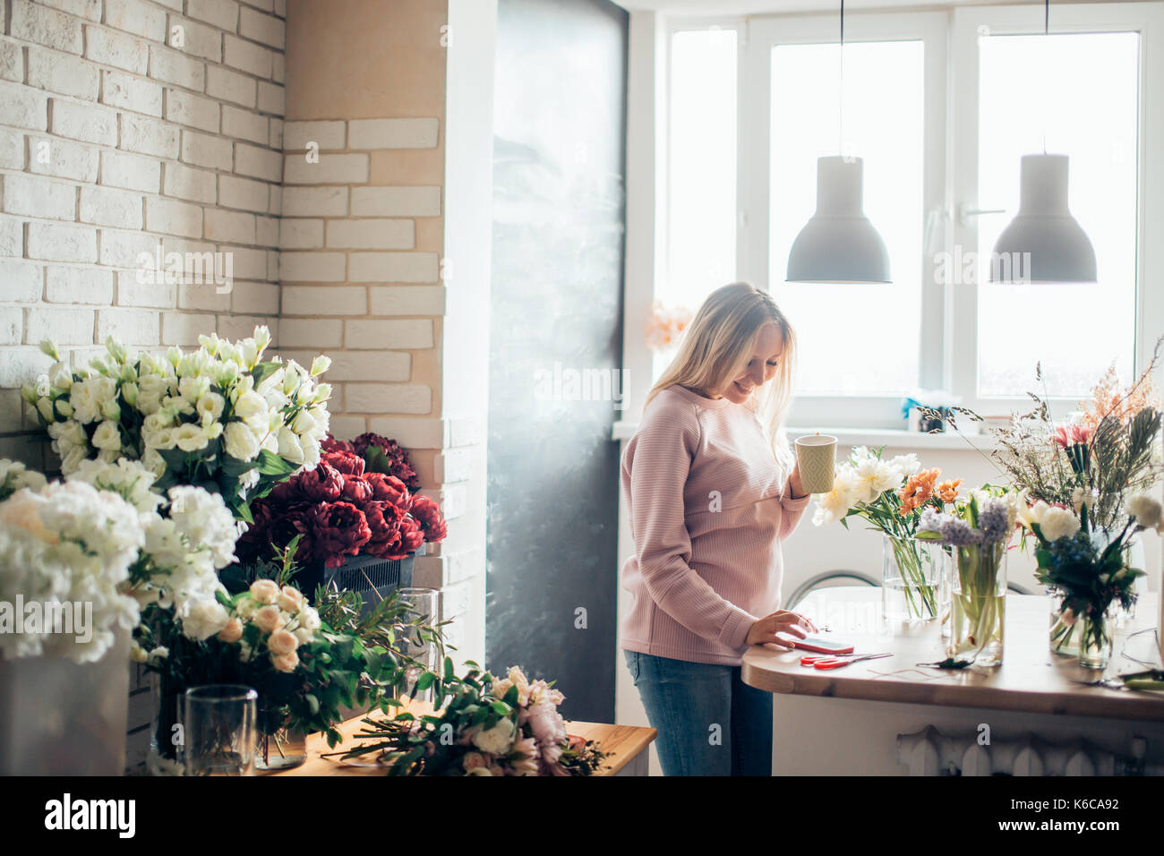 Florist at work. A woman in the process of making a summer bouquet of peonies, holds in her hand a cup of coffee. Tools and accessories florists need  - Stock Image