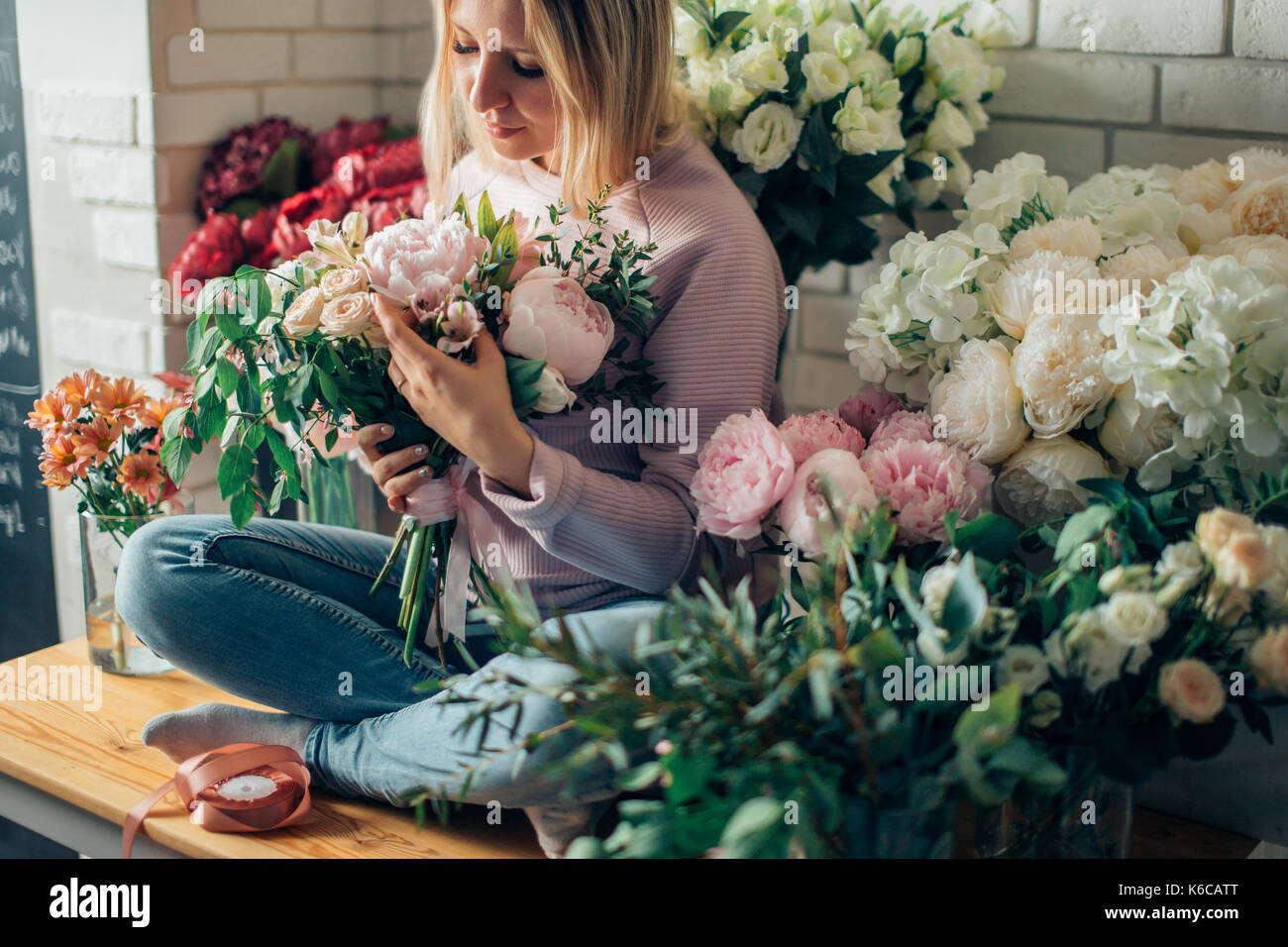 Florist shop in daylight. Woman holding beautiful bouquet of flowers. Florist with her work. Stylized tender photo with hipster filter. - Stock Image