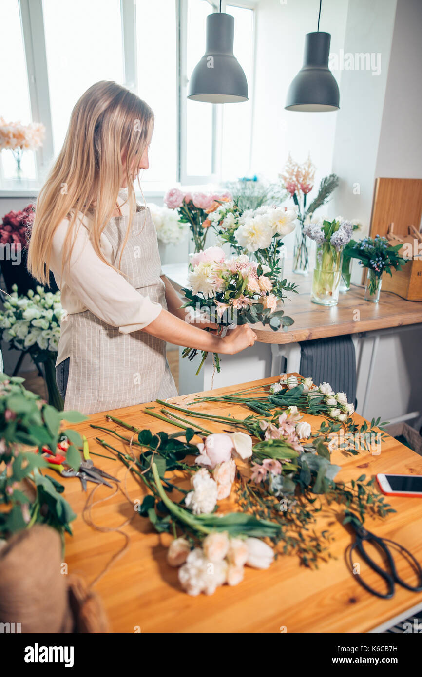 Small business. Male florist unfocused in flower shop. Floral design studio, making decorations and arrangements. - Stock Image