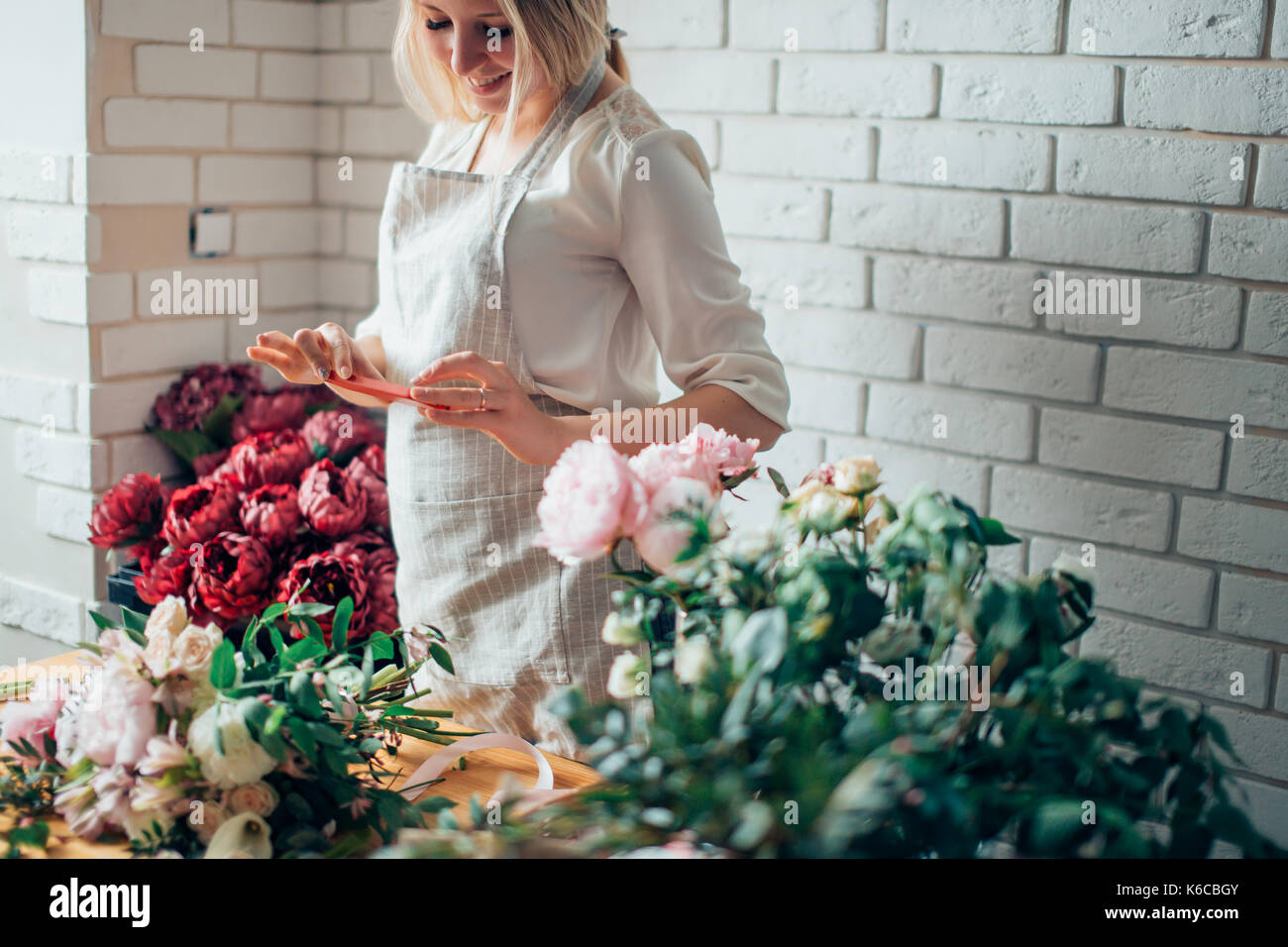 woman florist taking pictures of flowers with mobile phone - Stock Image