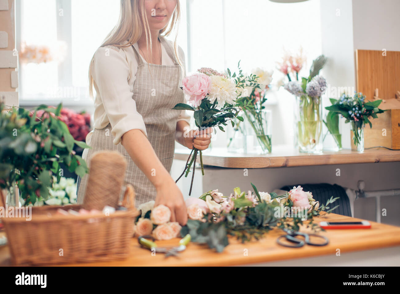 florist takes the scissors from the wooden table - Stock Image