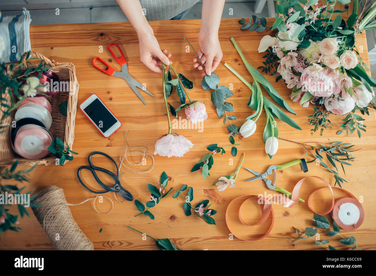 hands of florist against desktop with working tools and ribbons on wooden background - Stock Image