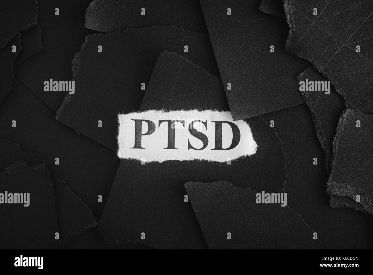 Post Traumatic Stress Disorder. Torn pieces of black paper and words Post Traumatic Stress Disorder. Concept Image. Black and White. Closeup. - Stock Image