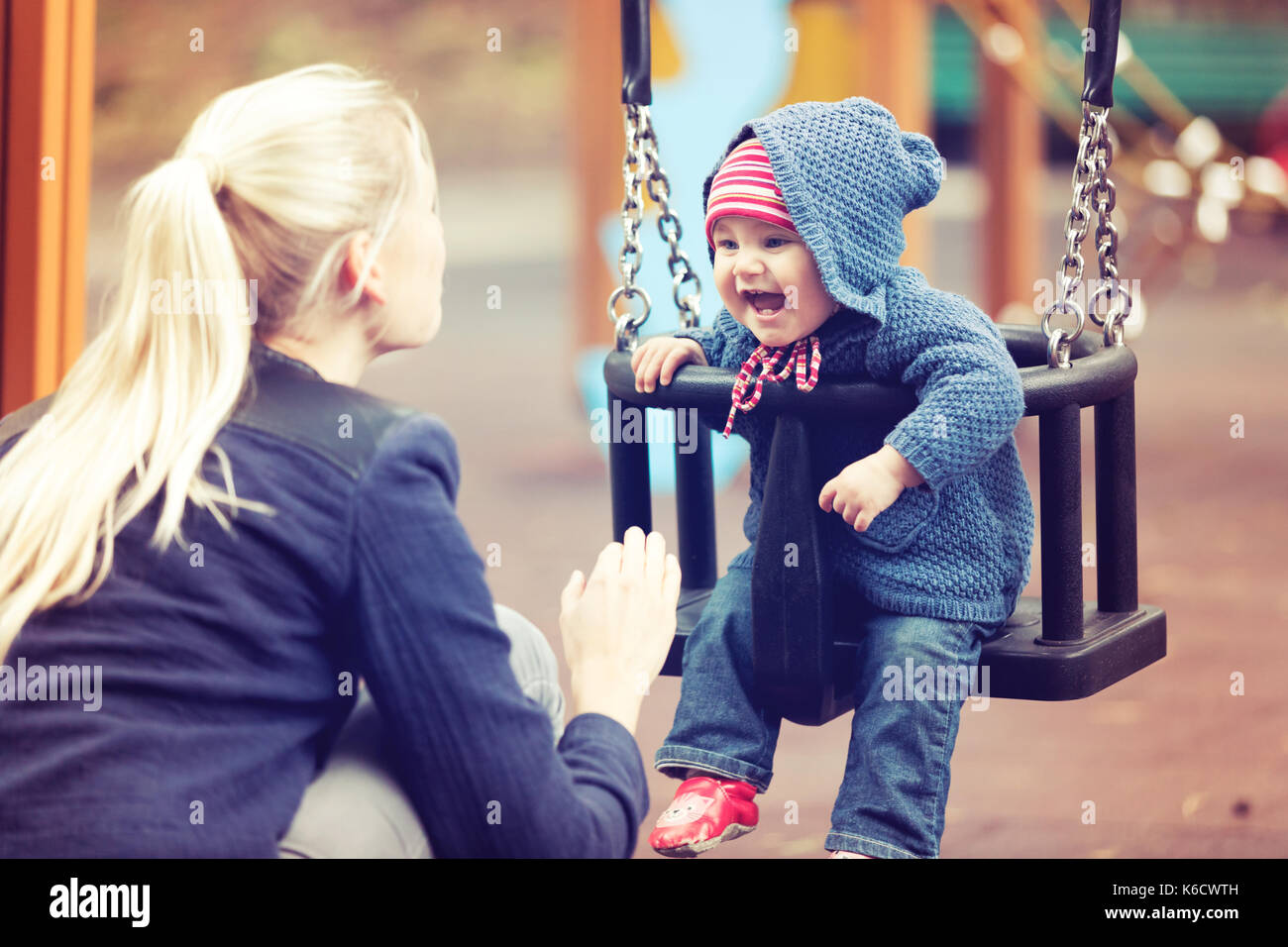 mother with her child having fun on playground swing on autumn day - Stock Image