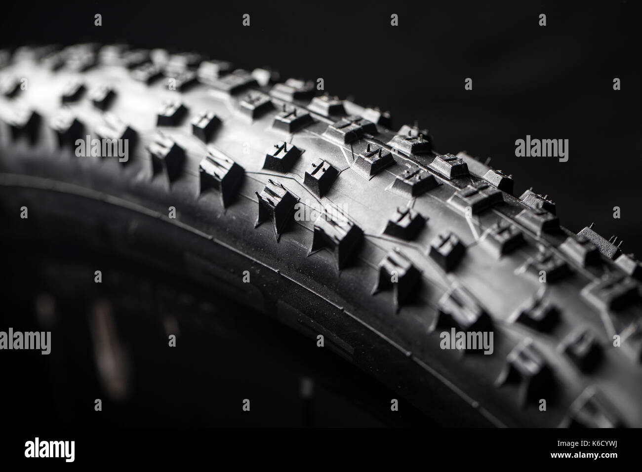 Modern MTB race mountain bike tyre isolated on black background in a studio - Stock Image