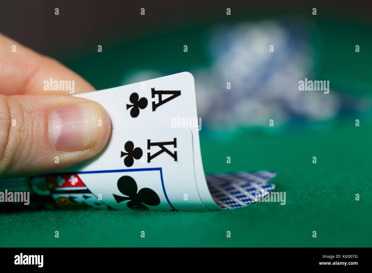 Man Hand Holds Ace with King and Poker Chips - Stock Image
