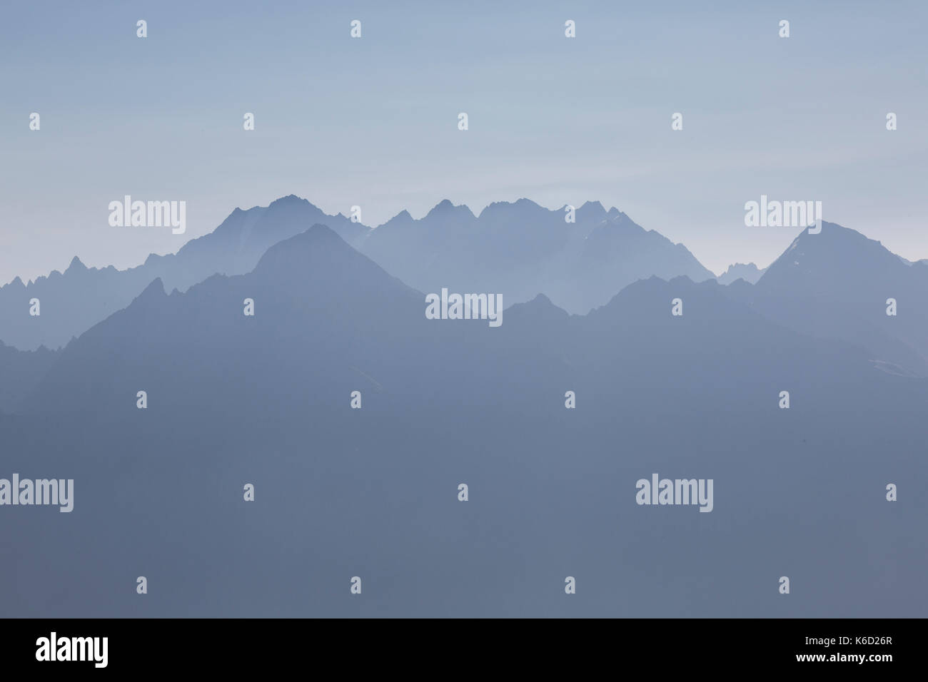 Mountain skyline showing grey coloured peaks and summits in the early morning light. Khaki mountain range in Georgia. - Stock Image